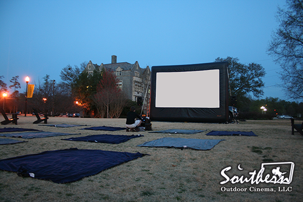 Blankets are setup in front of an inflatable movie screen on campus for a movie