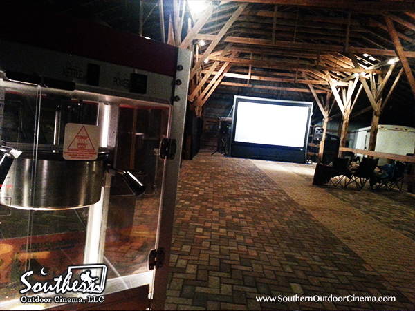 A silent inflatable movie screen setup inside a barn