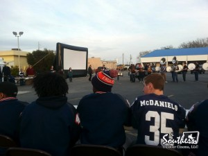 Football Game shown on outdoor movie screen.